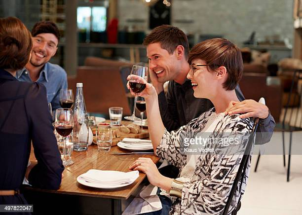 Friends laughing together at dinner with wine