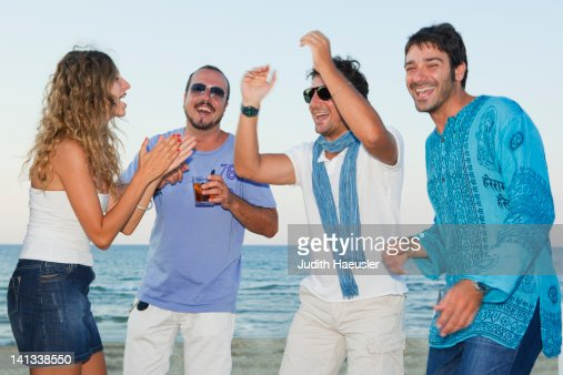 Friends laughing together on beach : Stock Photo
