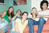 Friends laughing watching TV together