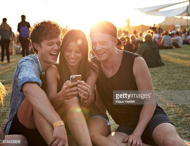 Friends laughing, while looking at smartphone