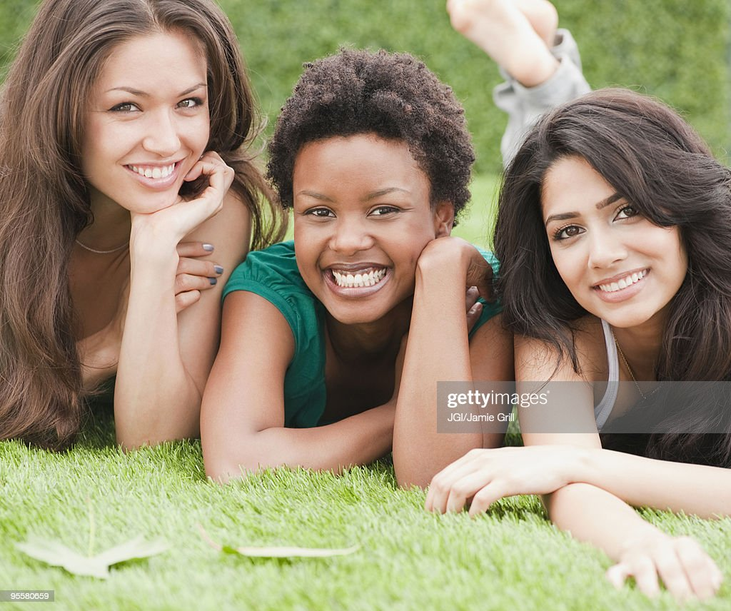 Friends laying and relaxing in grass : Stock Photo