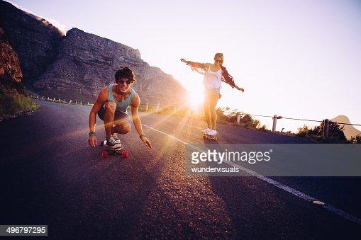Amis Faire du longboard sur la route au coucher du soleil