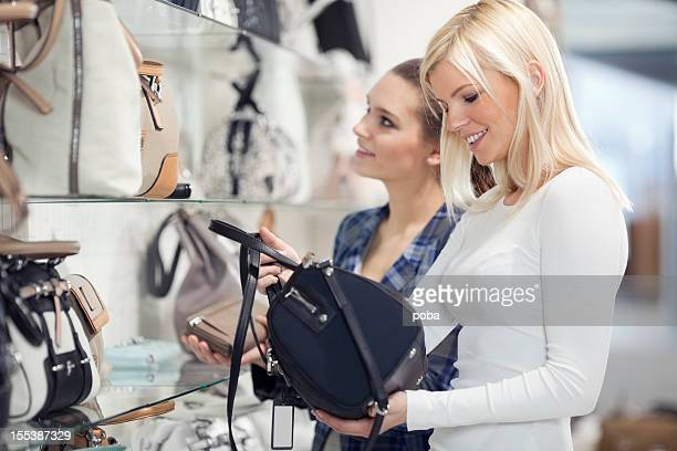 friends looking and buying  handbags   in department store