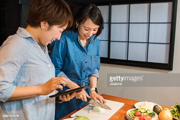 Friends looking at a digital tablet and cooking together