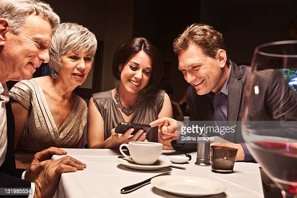 Friends looking at camera phone in restaurant
