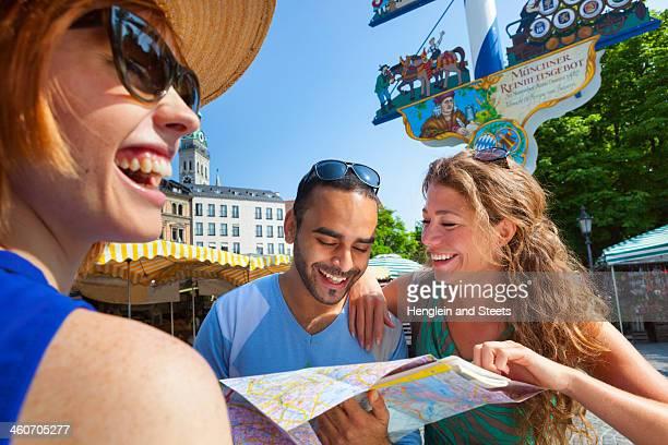 Friends looking at map in Munich Viktualienmarkt, Munich, Germany