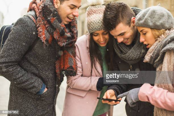 Friends looking at mobile phone in the city