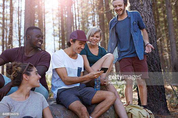 Friends looking at phone and laughing in forrest