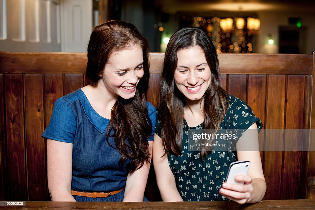 Friends looking at smartphone. : Stock Photo