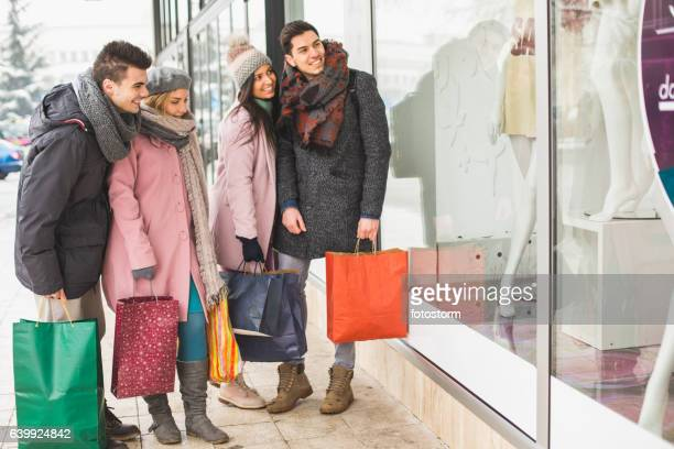 Friends looking at store window