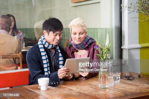 friends looking at ipad sitting at outdoor cafe : Stockfoto