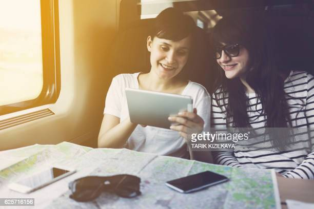 Friends looking at tablet pc, travelling in a train