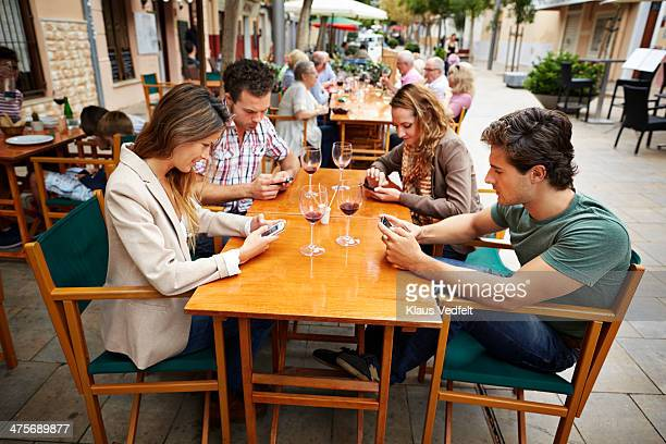 4 friends looking at their phones, while at café
