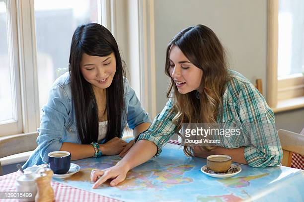 Friends looking at world map together.