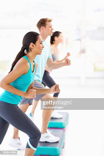 Friends Looking Away While Doing Step Aerobics In Gym