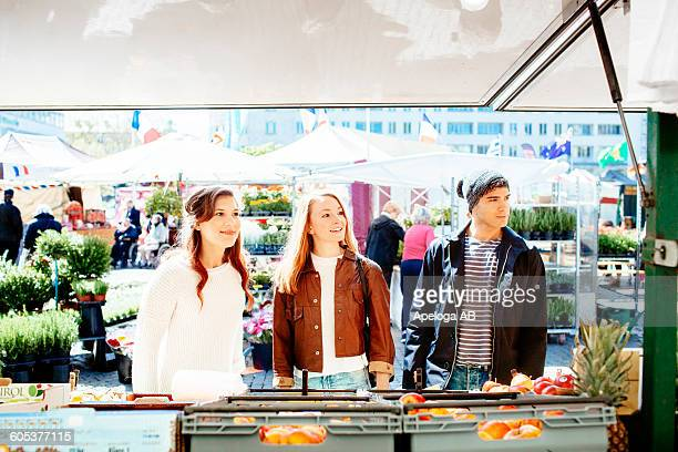 Friends looking away while shopping at stall in market