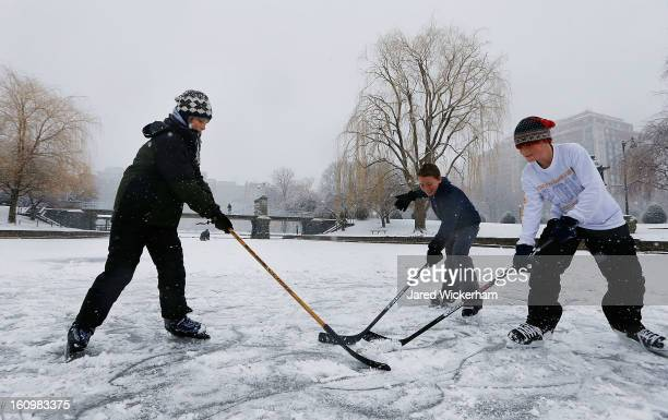 Friends Louis Lapsley Andreas Frank and Jackson Greeley play a game of ice hockey on the frozen duck pond in Boston Common on February 9 2013 in...