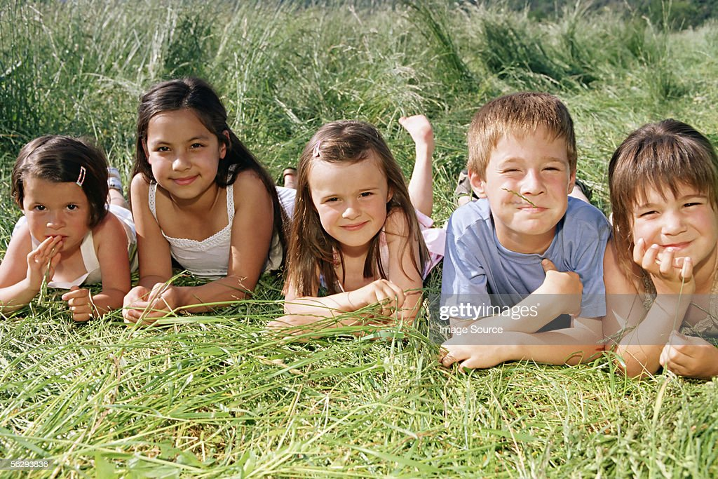Friends lying in the grass : Stock Photo