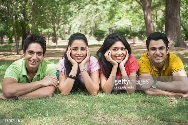 Friends lying side by side in a park, Lodi Gardens, New Delhi, Delhi, India