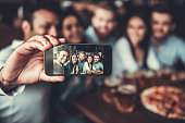 Selfie time! Handsome friends making selfie and smiling while resting at pub.