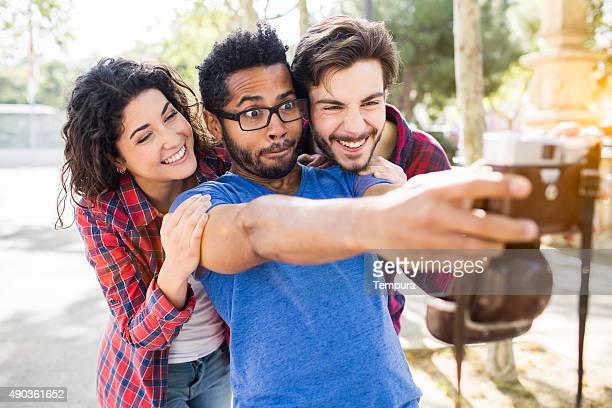 Amis faire un selfie avec un appareil photo rétro.