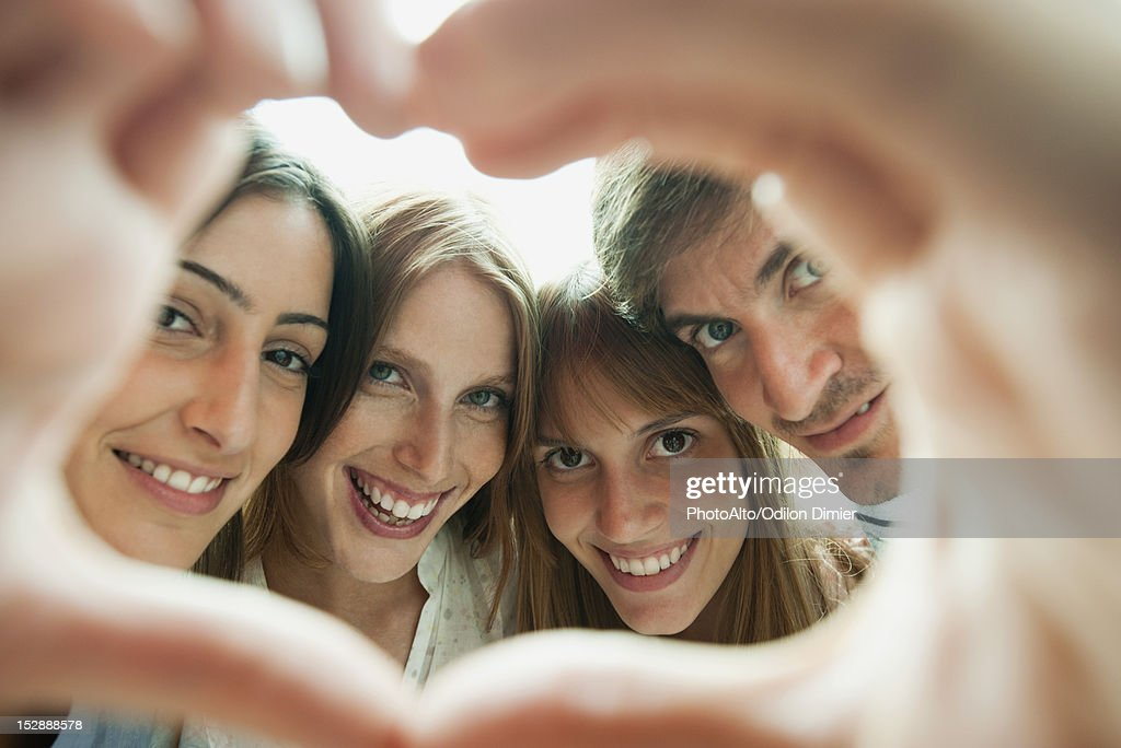 Friends making heart-shaped finger frame, portrait : Stock Photo
