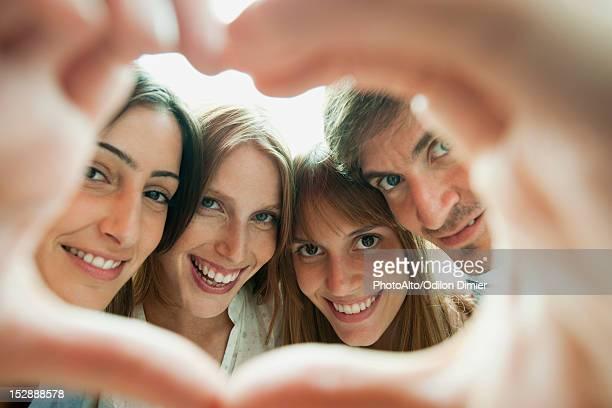Friends making heart-shaped finger frame, portrait