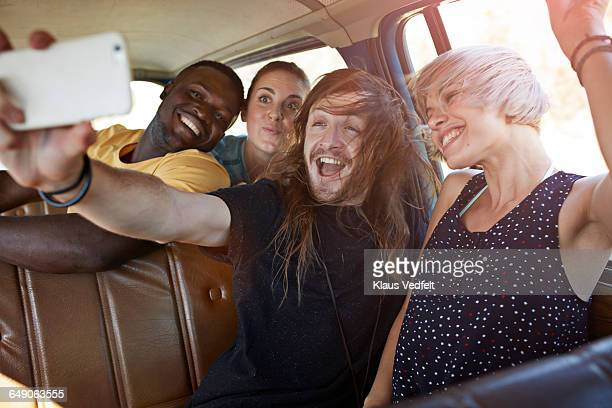 Friends making selfie while riding car