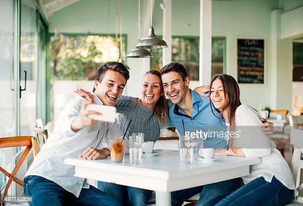 Amigos haciendo Selfie con smartphone en el restaurante.