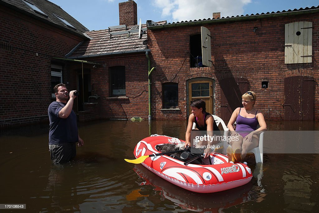Friends Malte, Stephanie (C) and Sandra, as well as Stephanie's dog Chewbaca, take in sunshine on a hot day while relaxing in the yard of their flooded home near the swollen Elbe river on June 7, 2013 in Elster, Germany. Floodwaters that have devastated parts of Saxony and Thuringia are now moving north, threatening towns along the Elbe and Saale rivers all the way to Hamburg. Eastern and southern Germany are suffering under floods that in some cases are the worst in 400 years. At least four people are dead and tens of thousands have evacuated their homes.