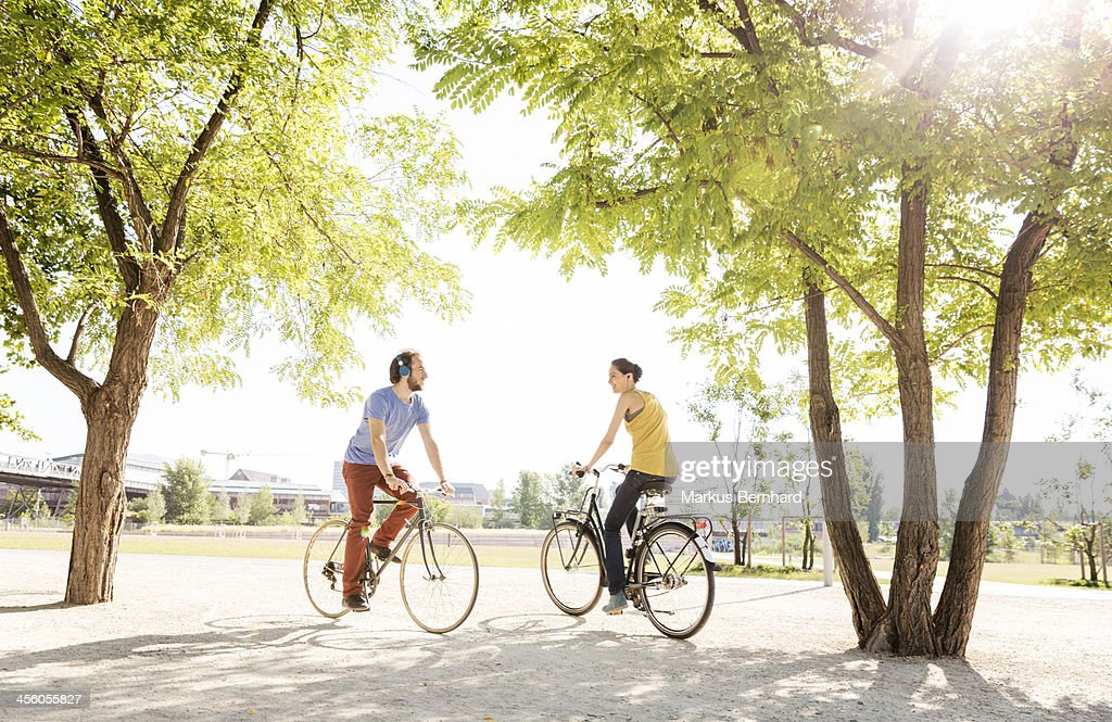 Friends meet in park on bicycles.