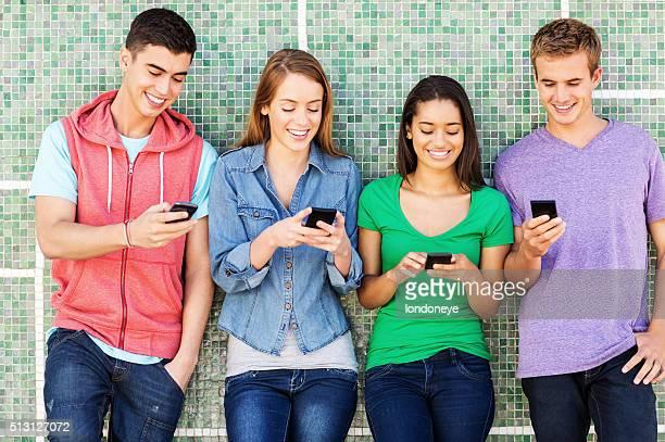 Freunde SMS auf Intelligente Handy stehend gegen die Wand