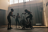 Woman exercising on air bike at gym with friends motivating. Female using air bike for workout at cross training gym with friends.