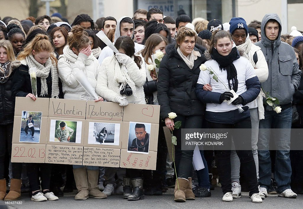 Friends of Laurent, Valentin (pictures foreground) and Gnilane, the two teenagers and their sister, aged 16, 14 and 9, found dead by their father, on February 22, 2013, in Dampmart, east of Paris, mourn during a 'marche blanche' (white march) of homage to the victims on February 23, in the streets of the village. The children were found throat-cutted at their home. The mother, who was first unreachable, was found later by policemen at some relatives's home in Paris and hospitalised following a psychiatric examination.