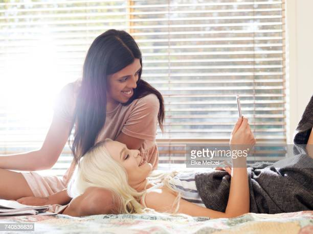 Friends on bed looking at smartphone smiling