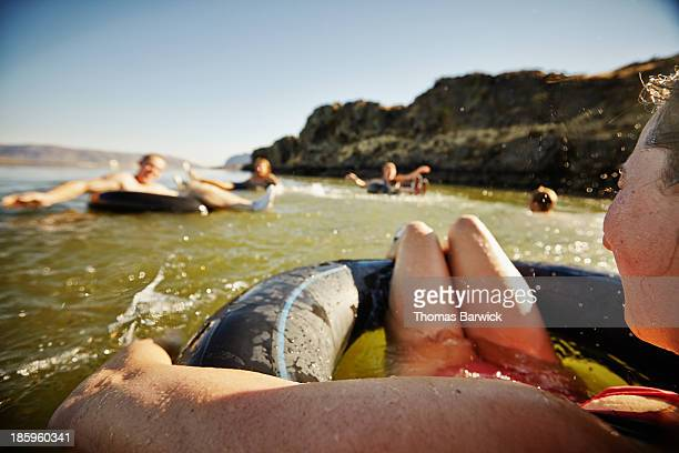 Friends on inner tubes smiling and laughing