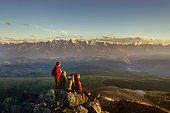 Four friends on mountain top looking to sunset