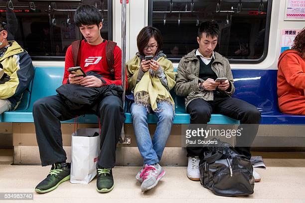 Friends on Phones Riding on Subway Train, Taipei, Taiwan