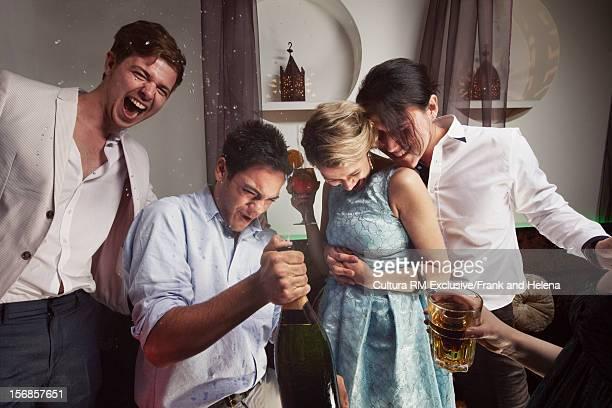 Friends opening champagne in nightclub