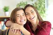 Front view portrait of a two happy friends or sisters posing smiling and looking at you with a homey background