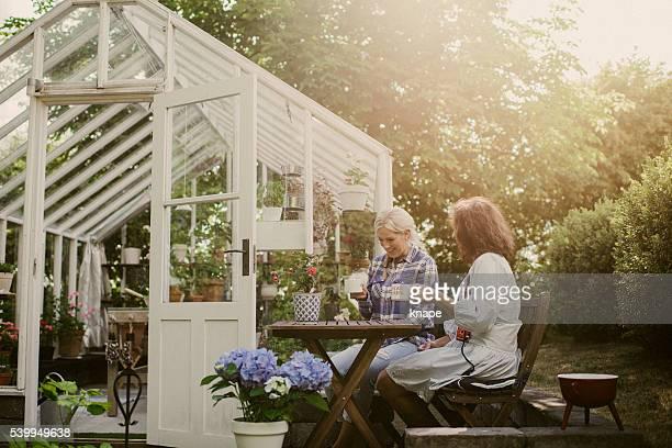 Friends outside greenhouse having coffee break