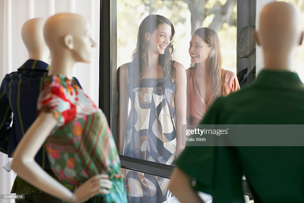 Friends outside of boutique window : Stock Photo