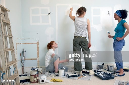 Friends painting doors and windows on the wall : Stock Photo