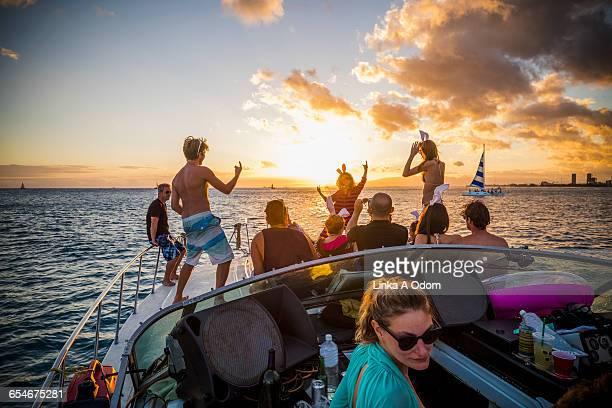 Friends party on yacht at sunset