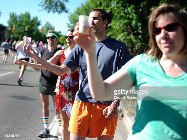 Friends pass out beer to runners less than a mile from the finish line during Bolder Boulder 10k Race on Monday morning May 31 in Boulder Diego James...