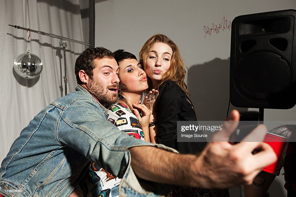 Friends photographing themselves at party : Stock Photo