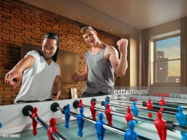 Amis jouent au football de table. Une seule équipe émotionnellement réjouit victoire