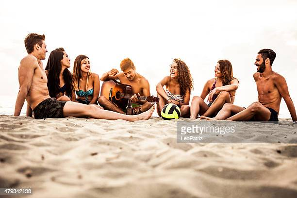 Friends playing and singing on the beach
