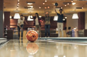 Happy young friends are having fun while playing bowling together, ball in focus
