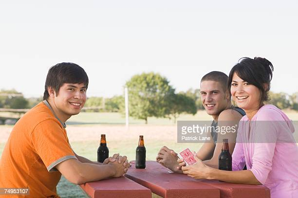 Friends playing card game and drinking beer